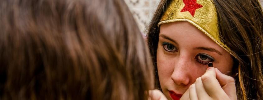 Una ragazza vestita da eroina che si trucca allo specchio