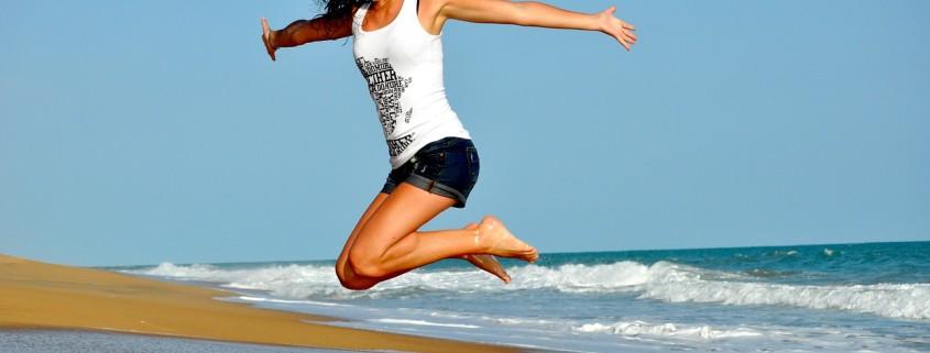Donna al mare che salta felice