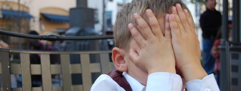 Bambino che si vergogna con mani agli occhi