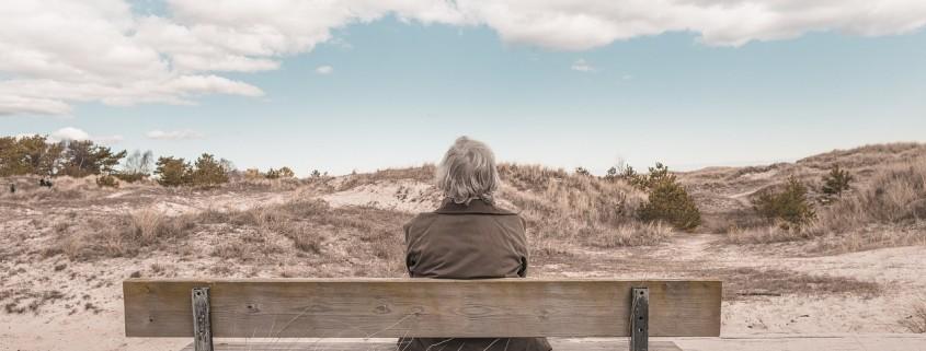 Un uomo che aspetta su una panchina, davanti ad un orizzonte infinito.