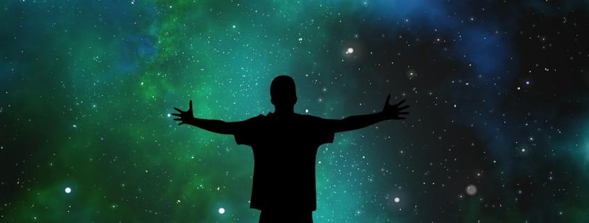 Un uomo che apre le braccia osservando un cielo di stelle luminose