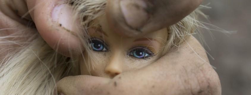 una barbie schiacciata da un dito maschile